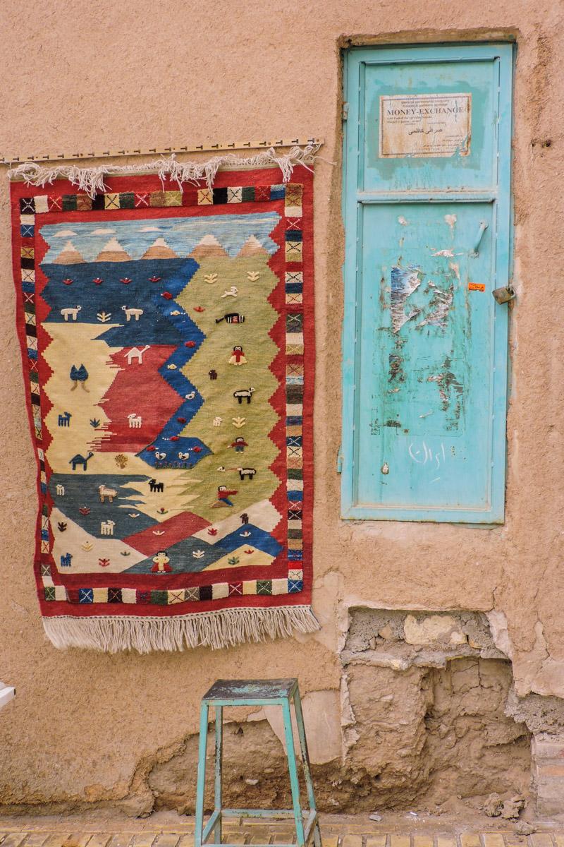 Una facciata del centro storico di Yazd. Un tappeto tradizionale appeso e una porticina blu non più utilizzata