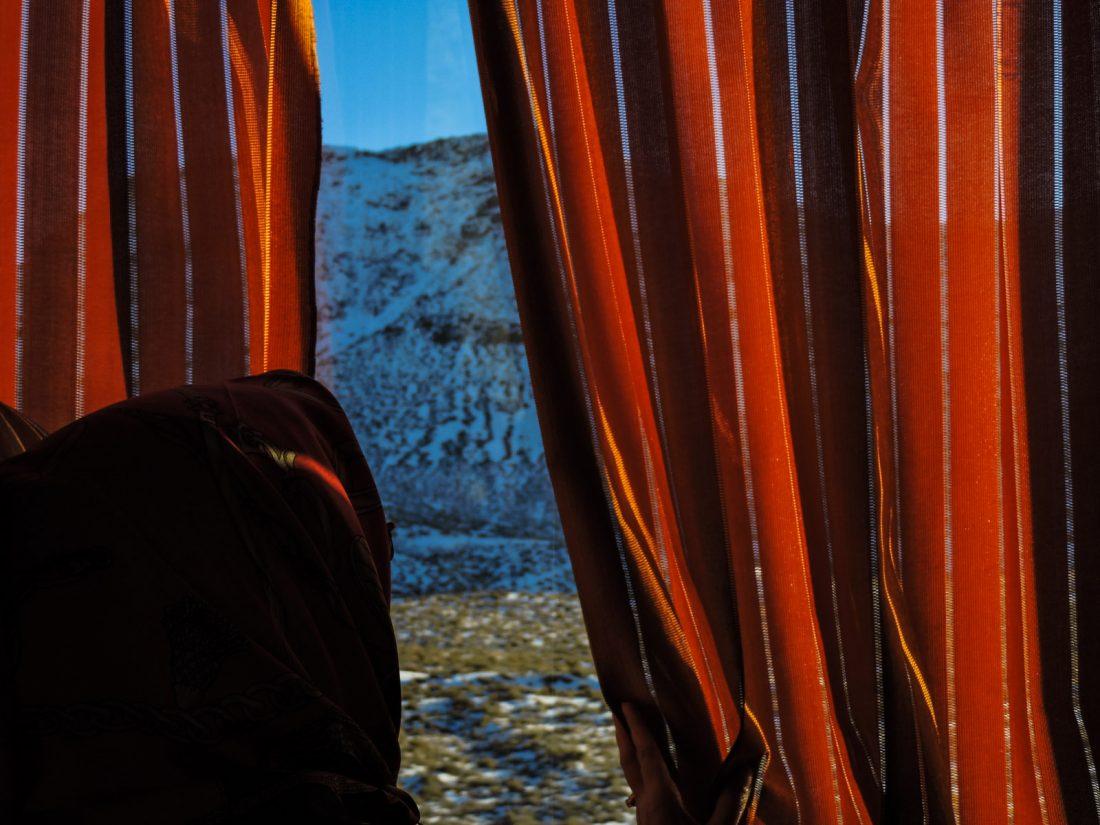 Alle scosta la tendina del finestrone del bus per osservare la neve nel deserto durante il viaggio tra Yazd e Esfahan