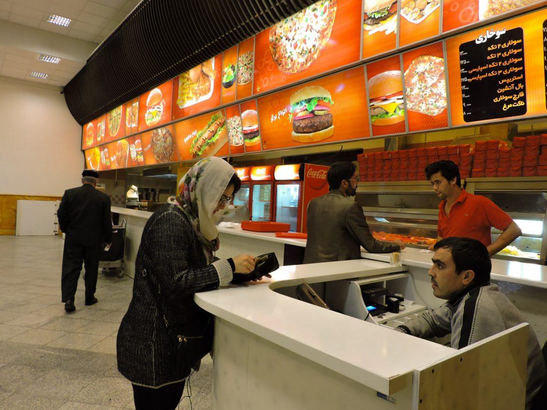 Alle compra degli hamburger in un autogrill stile McDonalds durante uno stop dell' autobus tra Shiraz e Esfahan