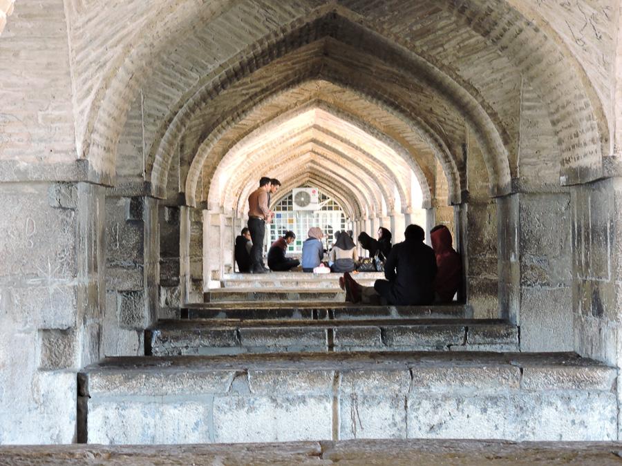 Giovani che si rilassano sotto gli archi del Khaju bridge