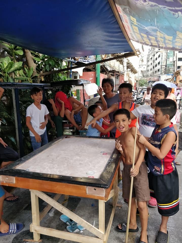 bimbi giocano al biliardo nel barangay 262 di Manila