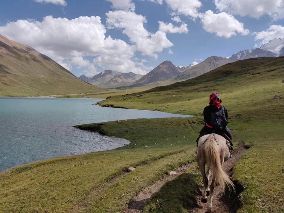 Cavalcando sul lago Kol Ukok con i ghiacciai all'orizzonte