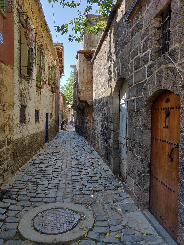 Vicoli di Diyarbakir, a destra le mura in basalto nero che caratterizzano l'architettura in città